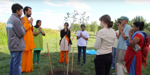 People stand before tree seedling with hands folded in prayer
