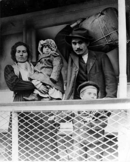 Immigrant family on a ship. Man holds their bundle of possessions on his back.