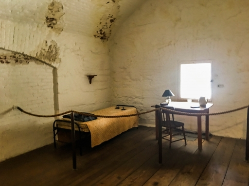 A bed and a desk near a window in a cell.