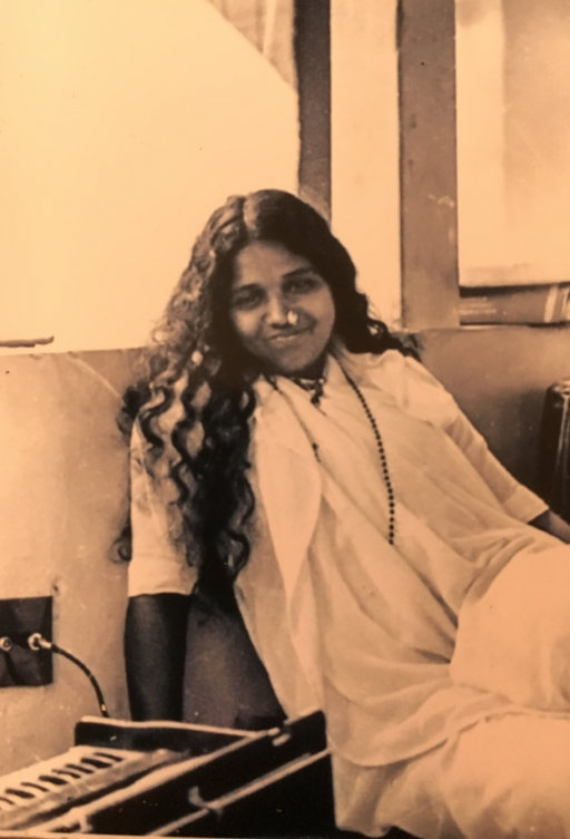photo of young Indian woman sitting near a window with long hair down