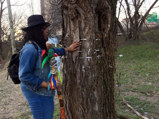 A black woman in a hat stands next to a tree with tags hanging from it.