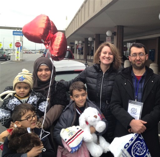 A Syrian refugee family poses in front of the airport after being resettled to Ohio.
