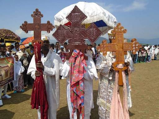Three people hold large Ethiopian crosses as they walk down the street