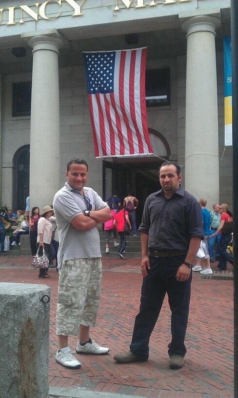 Two men meet underneath a US flag