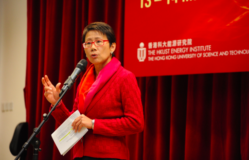 A woman in a red suit at a podium