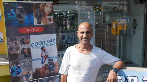 A man in a light T-shirt poses in front of a shop