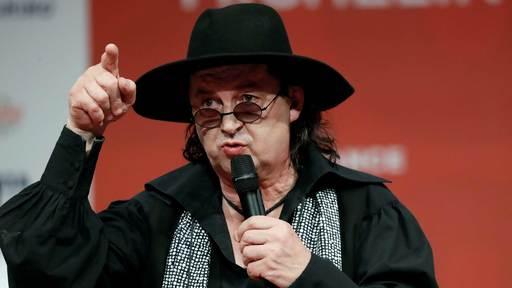 A man wearing a wide brimmed black hat speaks