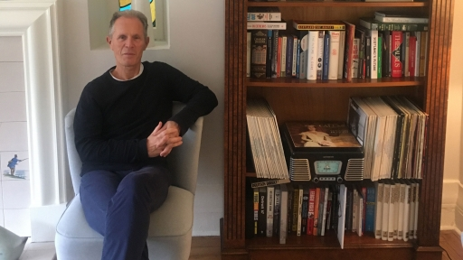 A portrait of Blair Jenkins sitting in his stair next to a book case