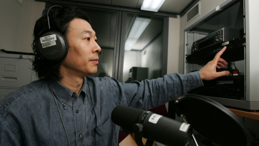 A man wearing headphones speaks into a microphone.