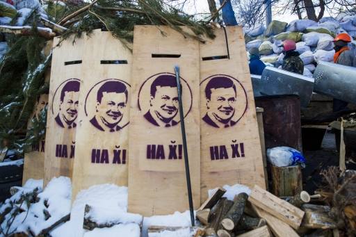 """Members of various anti-government paramilitary groups pass through barricades during a show of force in Kyiv, Jan.29, 2014. Pictured on the boards in the foreground is Ukrainian President Viktor Yanukovych. The writing reads, """"Get Out!"""""""