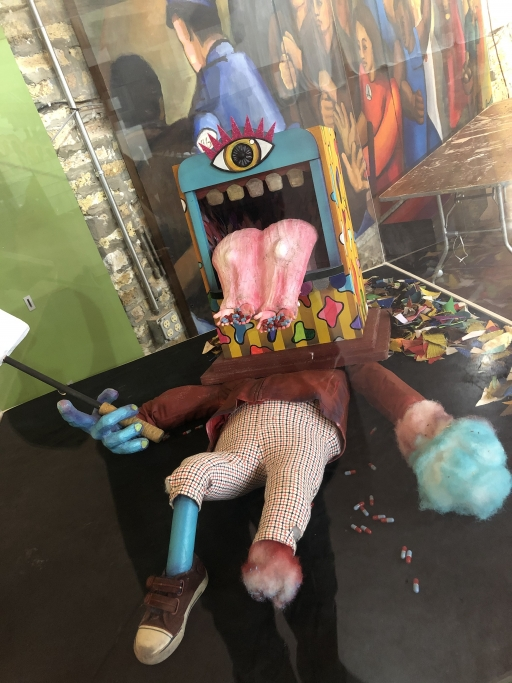 A puppet prop lays on a floor. It has a single eye, and a large pink tongue coming out of a square shaped head