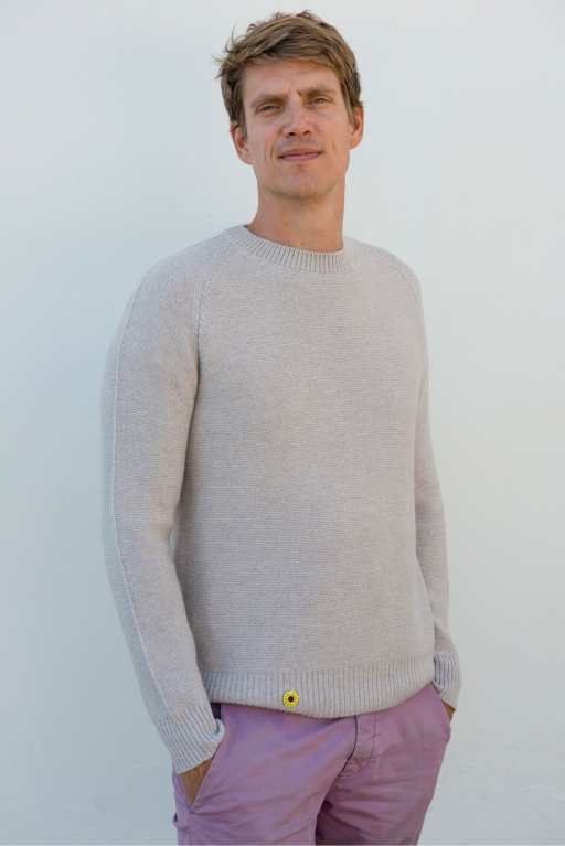 A white man in an off-white sweater and pink pants poses