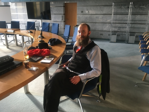 A man with a long beard and glasses in a dark suit sits at a table