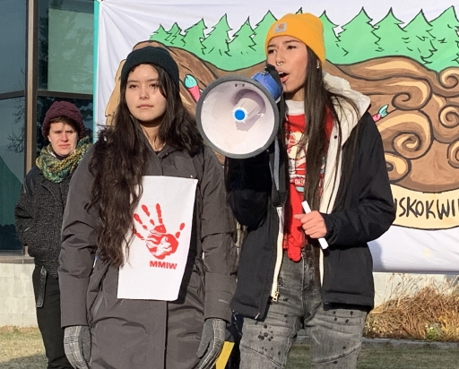 Two young women speak with a megaphone to announce climate emergency