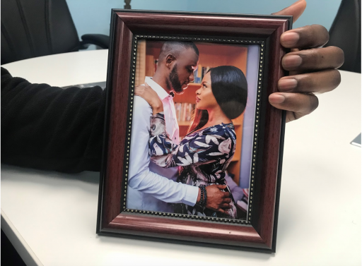 A man holds a framed photo of a couple