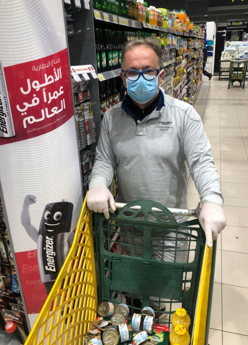 A man with a face mask and gloves shops in a grocery store