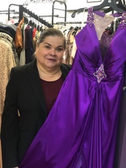 Ida Ann Pedregó poses with a dress at her boutique in Douglas, Arizona. She closed the store indefinitely March 21 due to the coronavirus outbreak.