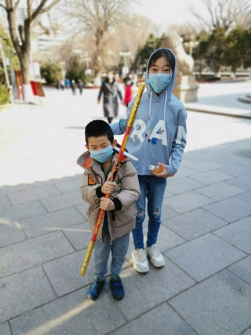 Two children play outside with face masks on.