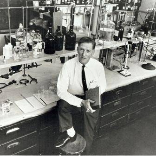 A black and white photograph of Cal-Tech scientist Arie Haagen-Smit who is standing with one foot on a stool in a laboratory.