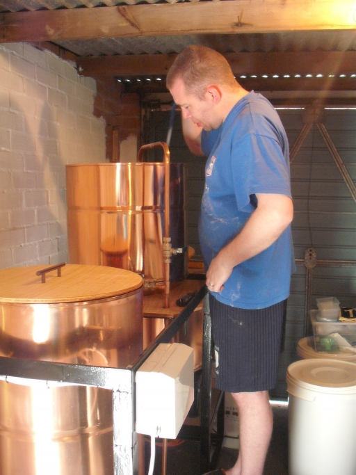 A man stands over a brewer's kit
