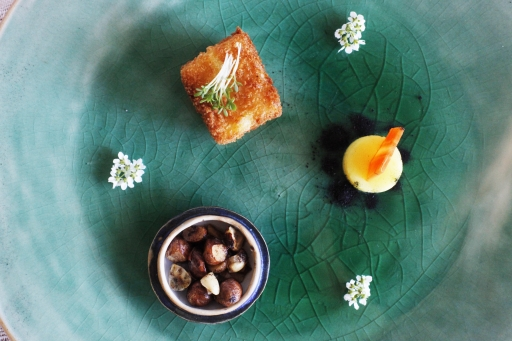 A poetic meal of three small dishes on a green plate