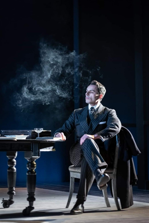 A man sits in a dark suit on stage with smoke around his face.