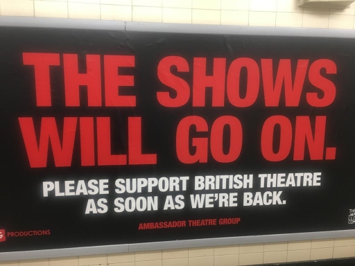 A red sign in a London tube station supports West End theaters.