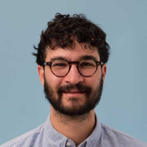 A man with a beard and glasses looks at the camera.