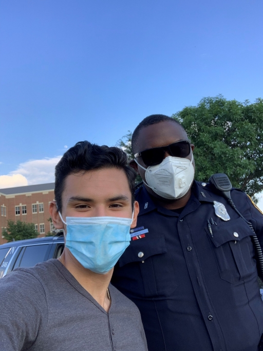 Izcan Ordaz, left, poses with a Fort Worth, Texas, police officer at a recent Black Lives Matter protest near his high school.