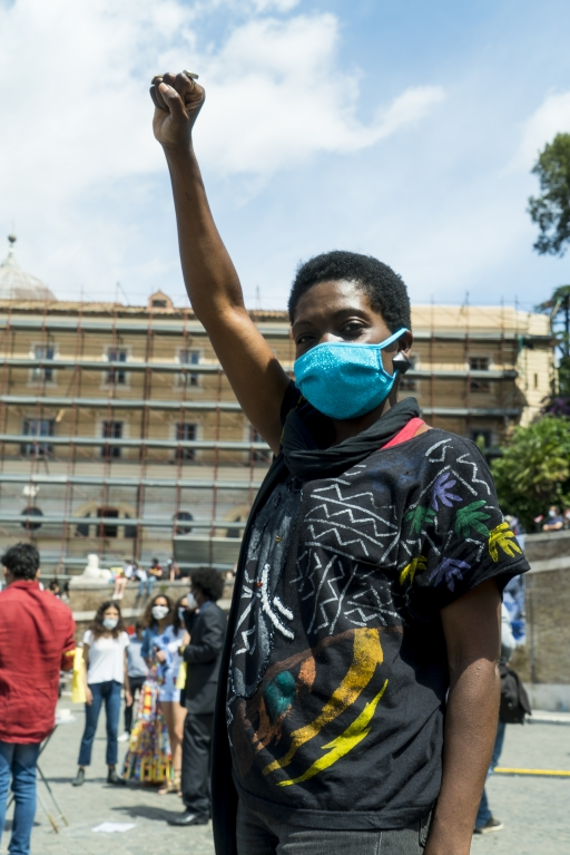 A Liberian woman with short afro wears a blue face mask at a protest
