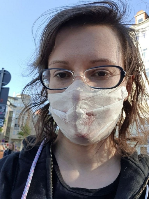 A woman with glasses wears a sweatshirt and a white face mask.