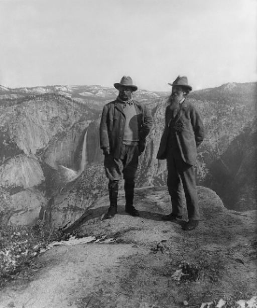 Black and white photo of two men wearing slacks, coats and hats, standing in an open landscape of rolling hills