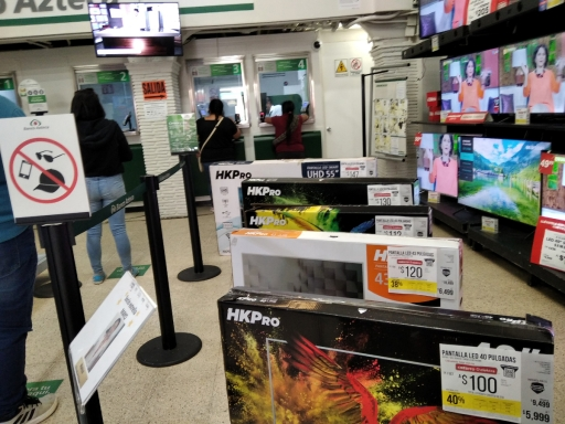 A line at a bank next to TVs for sale in the same space