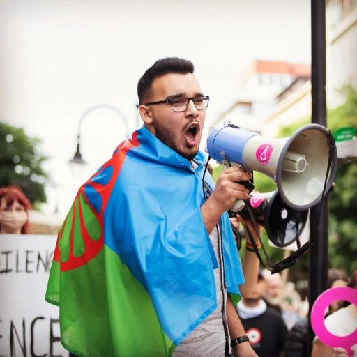 A man with glasses wears a green and blue flag draped around his shoulders.