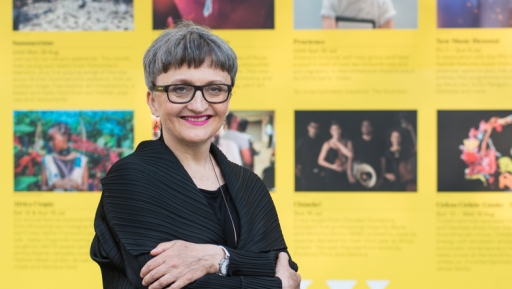 A white woman wearing glasses and a short hair cut smiles in front of yellow backdrop
