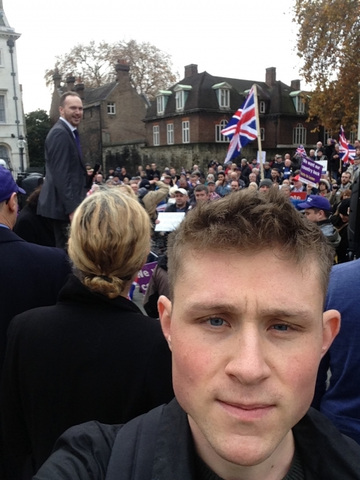 A white man with blond hair takes a selfie at a rally