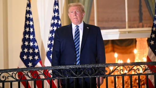 After pulling off his face mask, President Donald Trump poses atop the Truman Balcony of the White House following hospitalization at Walter Reed Medical Center, Oct. 5, 2020.