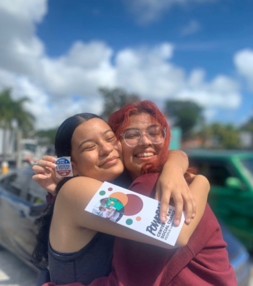 """Two young people embrace each other and show an """"I voted"""" sticker"""