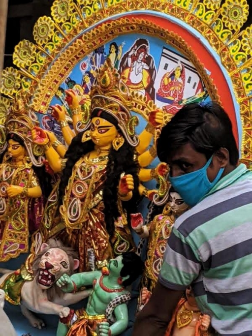 A man holds an ornate Durga idol in his arms while he wears a mask