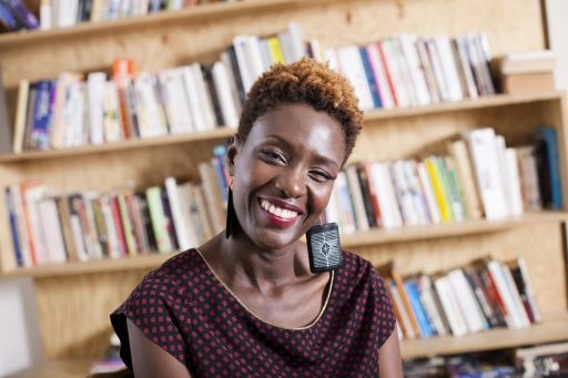 A Black woman with short hair wears earrings and a black and red blouse and smiles warmly in front of a large bookshelf.