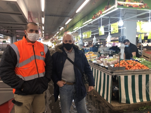 A man wearing an orange vest stands near his older friend at an indoor market