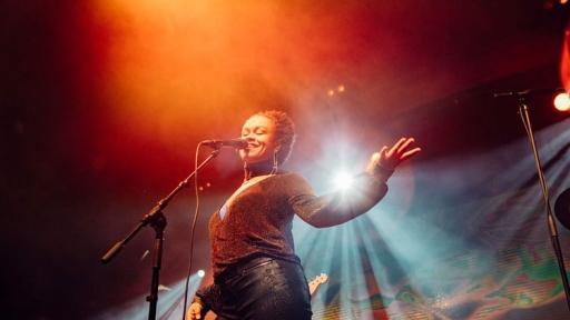 Ethiopian American singer Meklit Hadero is shown performing under orange and red lighting.