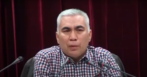 A man with silver hair speaks into a microphone wearing a plaid, button-down shirt