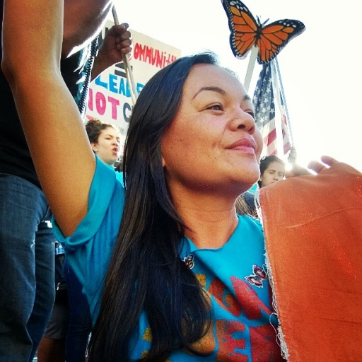 A woman wearing a blue shirt stands with a hand up and a monarch butterfly image near her.