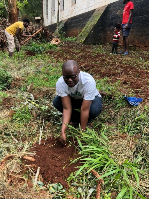 A Kenyan man plants a tree in a forest.