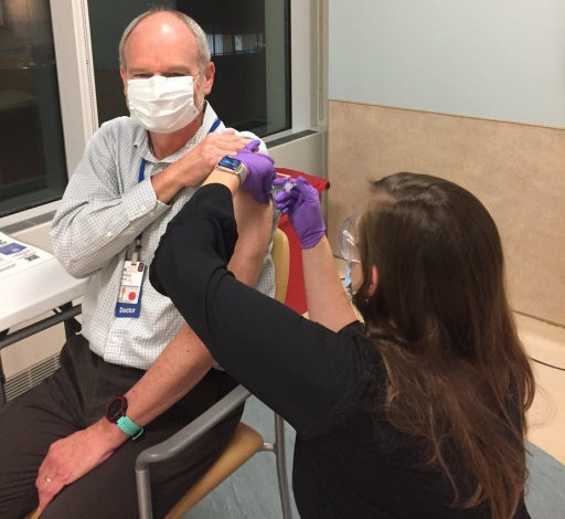 A white, older man wearing a white mask receives a shot in his arm by a younger woman with long brown hair whose face is toward the man.