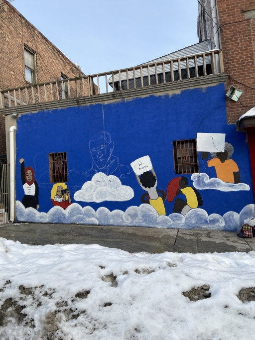 A photo of an unfinished mural in a snowy lot.
