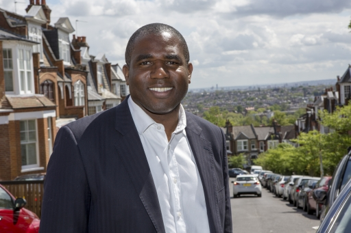 MP David Lammy poses outdoors for a photo wearing a dark suit and white button shirt