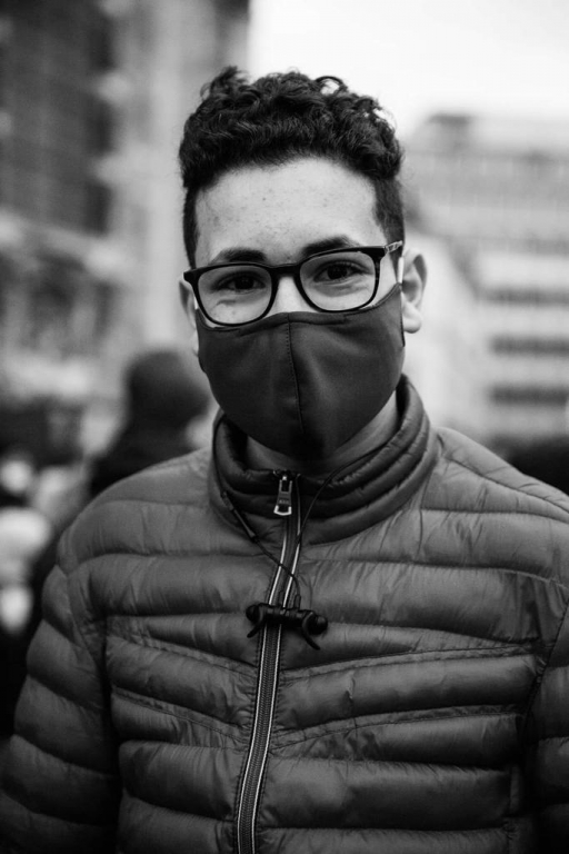 Sixteen-year-old Mohammed Amine wears glasses, a face mask and puffy jacket.