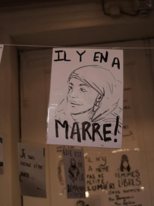 "A protest sign reads ""Il y'en a marre,"" or ""We've had enough of it."""